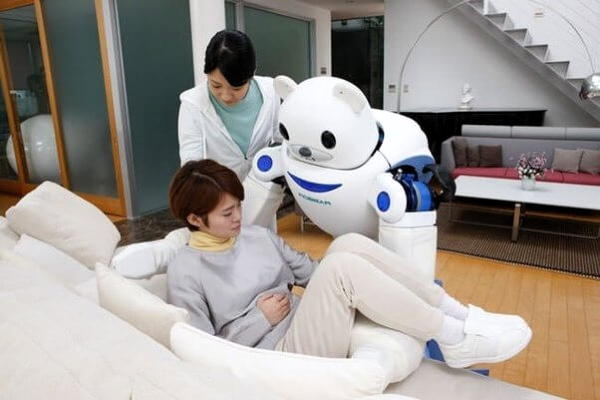 Friendly looking robot carries woman onto sofa